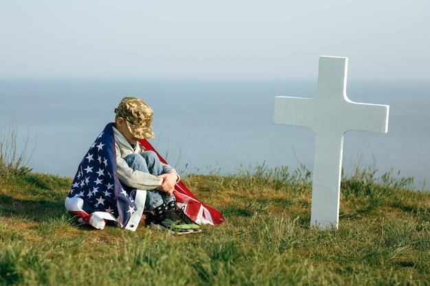Een jonge jongen in een militaire pet, bedekt met de vlag van de verenigde staten, zittend op het graf van zijn overleden vader. 27 mei herdenkingsdag