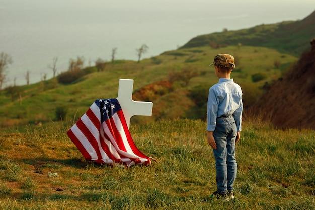 Een jonge jongen in een militaire pet groet het graf van zijn vader op herdenkingsdag