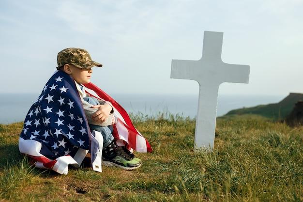 Een jonge jongen in een militaire pet, onder de vlag van de verenigde staten, zittend op het graf van zijn overleden vader. 27 mei herdenkingsdag