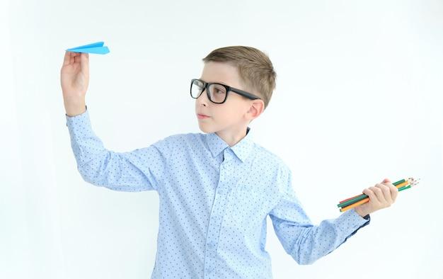 Een jonge jongen in een shirt houdt een papieren vliegtuigje en kleurpotloden vast, glimlachend.