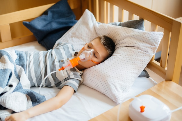 Een jonge jongen krijgt een inhalatie tijdens een longziekte. covid19, coronavirus, pandemie.