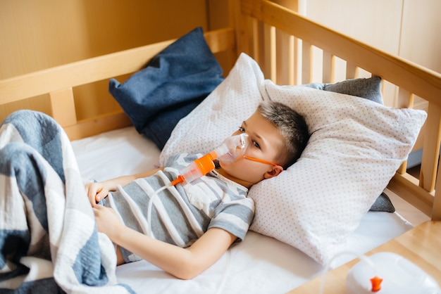 Een jonge jongen krijgt een inhalatie tijdens een longziekte. geneeskunde en zorg