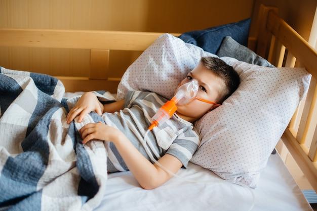 Een jonge jongen krijgt een inhalatie tijdens een longziekte. geneeskunde en zorg.