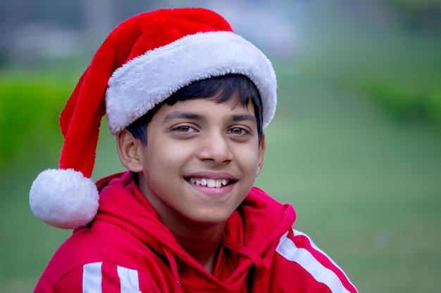 Een jonge jongen met een kerstmuts, glimlachend en kijkend naar de camera tijdens de kerstperiode