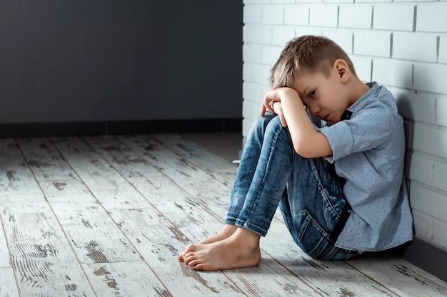 Een jonge jongen zit alleen met een droevig gevoel op school dichtbij de muur