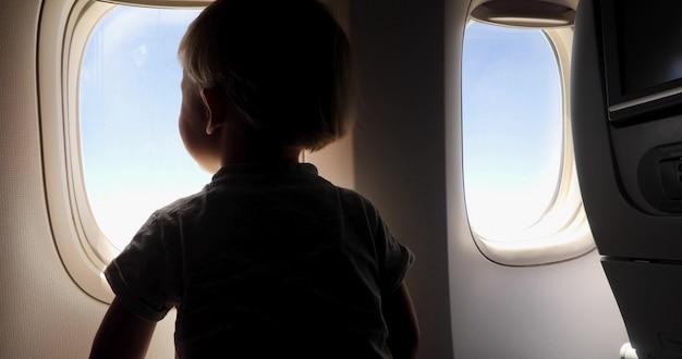 Een jonge jongenszitting op de zetel die uit een vliegtuigvenster kijkt terwijl het vliegen