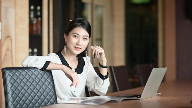 Een jonge kantoorvrouw zit met een computerlaptop aan de vergadertafel.
