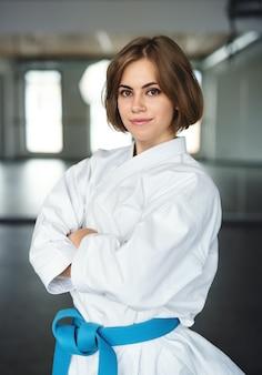 Een jonge karatevrouw die binnenshuis in de sportschool staat en naar de camera kijkt.