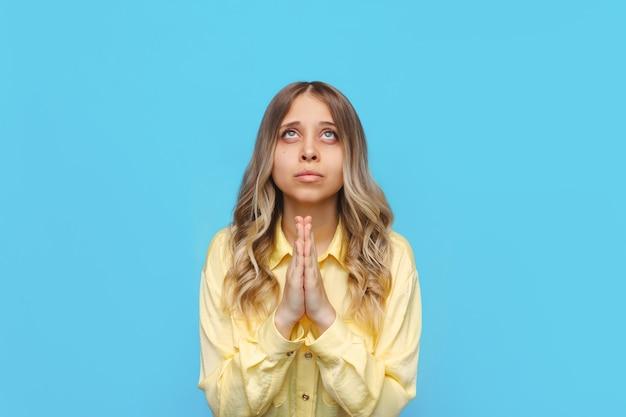 Een jonge kaukasische mooie blonde vrouw in een geel overhemd bidt omhoog kijkend naar de lucht met gevouwen handen dankzegging wens vragen om hulp, hoop of vergeving geïsoleerd op een lichte kleur blauwe muur