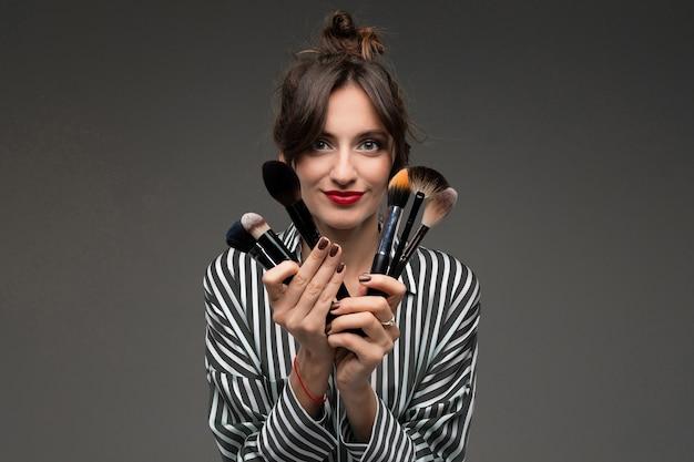 Een jonge kaukasische vrouw houdt make-upborstels die op grijze muur worden geïsoleerd