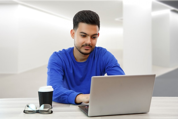 Een jonge kerel die achter een laptop zit op zoek naar werk op internet, zaken doet in het wereldwijde netwerk met een kopje koffie. op licht