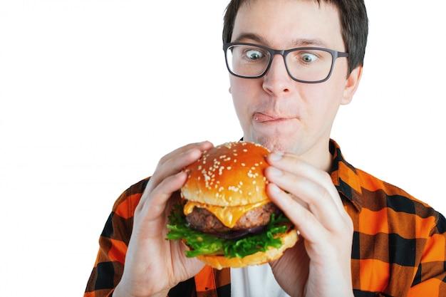Een jonge kerel die een verse hamburger houdt.