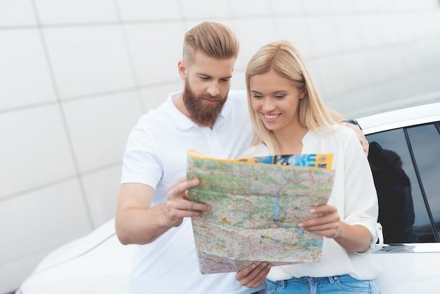 Een jonge kerel en een meisje kijken naar een kaart van snelwegen.