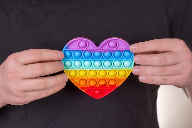 Een jonge kerel heeft een regenbooghart in zijn handen new fashion colorful silicone antistress pop it toy