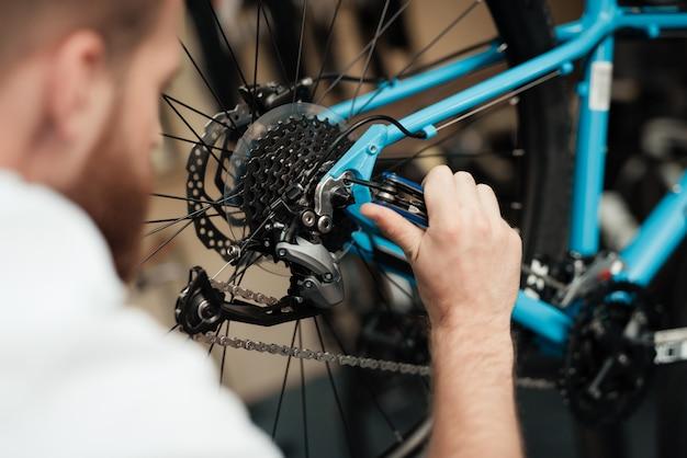 Een jonge kerel herstelt een fiets in winkel