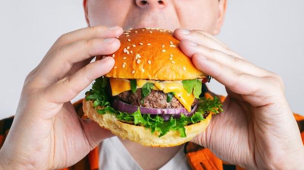 Een jonge kerel houdt een verse hamburger.
