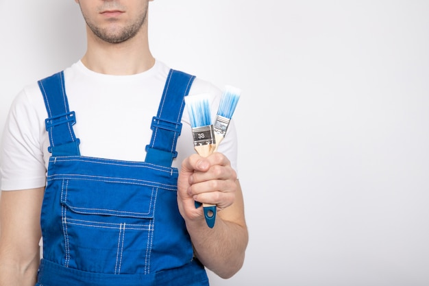 Een jonge kerel in blauwe overall houdt een bouwborstel in zijn hand.