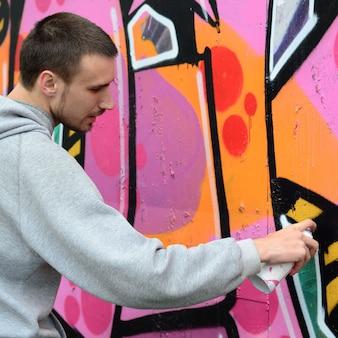 Een jonge kerel in een grijze hoodie schildert graffiti in roze en groen c