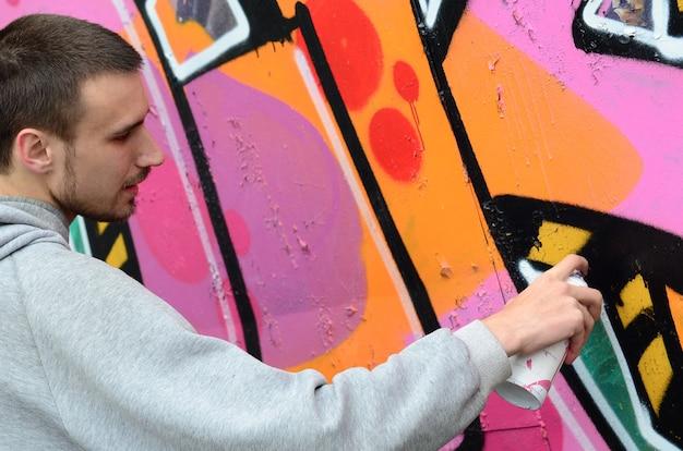 Een jonge kerel in een grijze hoodie schildert graffiti in roze en groen