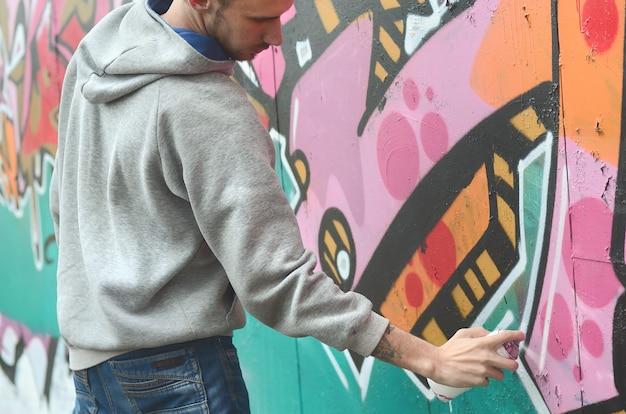 Een jonge kerel in een grijze hoodie schildert graffiti in roze