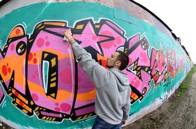Een jonge kerel in een grijze hoodie schildert graffiti