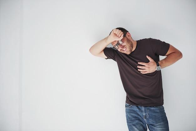 Een jonge kerel in vrijetijdskleding houdt het hart en het hoofd vast