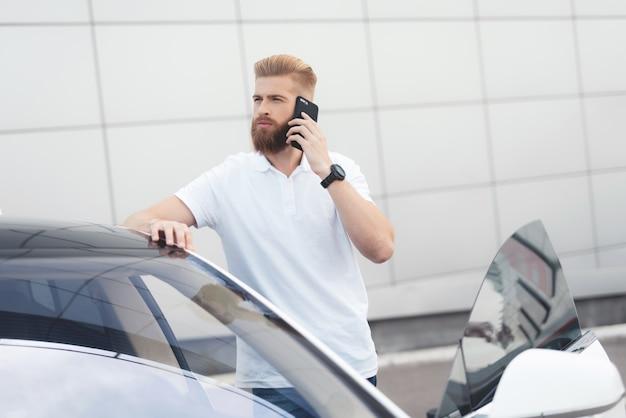 Een jonge kerel met een baard die op de telefoon spreekt