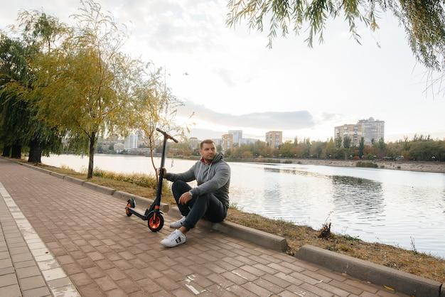Een jonge kerel rijdt in het park op een elektrische scooter op een warme herfstdag. wandeling in het park.