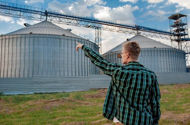 Een jonge kerel staat bij een graanpakhuis en toont met zijn hand