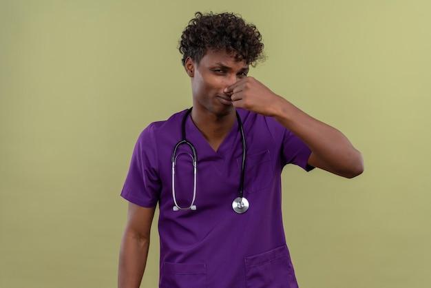 Een jonge knappe dokter met een donkere huid en krullend haar in een violet uniform met een stethoscoop die de neus vasthoudt vanwege de vreselijke geur op een groene ruimte