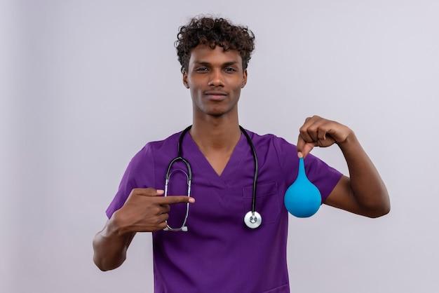 Een jonge knappe dokter met een donkere huid en krullend haar in violet uniform met een stethoscoop die duimen naar beneden toont terwijl hij met wijsvinger naar een klysma wijst