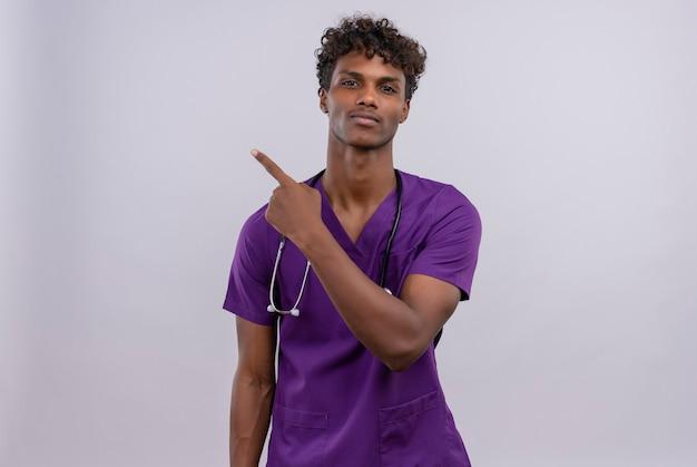 Een jonge knappe dokter met een donkere huidskleur en krullend haar in een violet uniform met een stethoscoop terwijl hij met de wijsvinger naar de linkerkant wijst