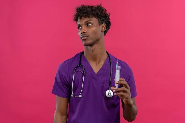Een jonge knappe donkere arts met krullend haar die violet uniform draagt met een stethoscoop die injectiespuit houdt