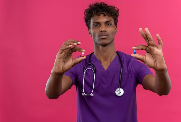 Een jonge knappe donkere arts met krullend haar die violet uniform draagt met een stethoscoop die pillen toont