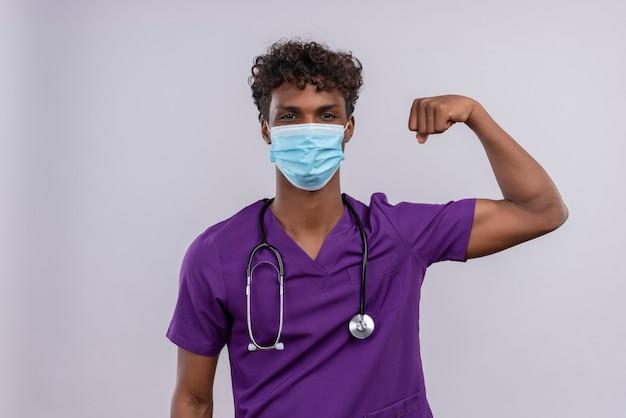 Een jonge knappe donkere arts met krullend haar die violet uniform draagt met een stethoscoop in een gezichtsmasker dat krachtgebaar toont