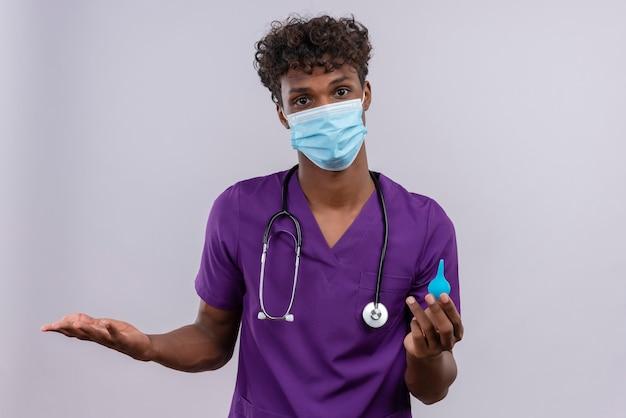 Een jonge knappe donkere arts met krullend haar die violet uniform draagt met een stethoscoop in een gezichtsmasker en een klysma vasthoudt