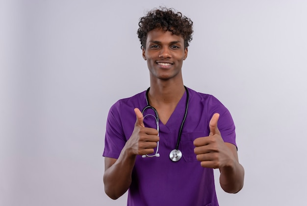 Een jonge knappe donkere arts met krullend haar die violet uniform met een stethoscoop draagt en duimen opdagen met een blij gezicht