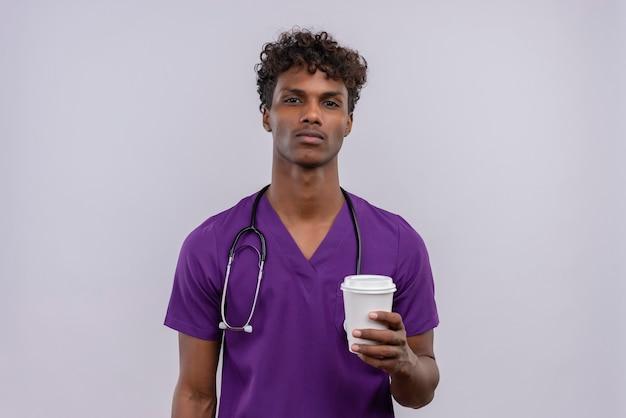 Een jonge knappe donkere arts met krullend haar die violet uniform met een stethoscoop draagt en een papieren kopje koffie houdt