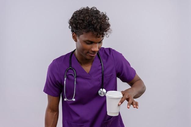 Een jonge knappe donkere arts met krullend haar draagt violet uniform met een stethoscoop en kijkt naar een papieren kopje koffie