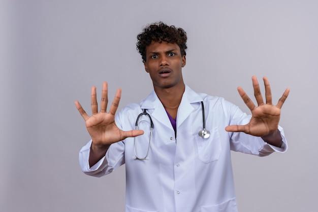 Een jonge knappe donkere arts met krullend haar, gekleed in een witte jas met een stethoscoop, hand in hand in stop of genoeg gebaar op een witte achtergrond