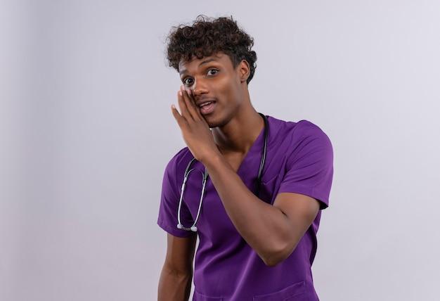 Een jonge knappe donkere arts met krullend haar in violet uniform met een stethoscoop die iets probeert te zeggen