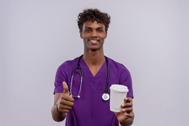Een jonge knappe donkere arts met krullend haar in violet uniform met een stethoscoop die papieren kopje koffie met duimen omhoog houdt