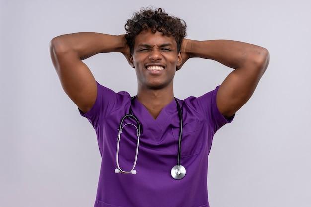 Een jonge knappe donkere arts met krullend haar in violet uniform met een stethoscoop hand in hand op het hoofd met gesloten ogen