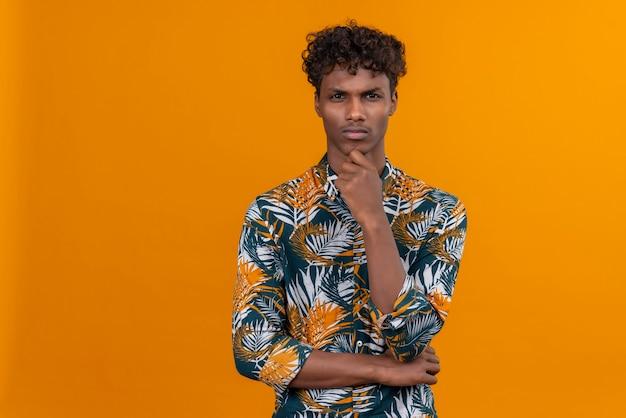 Een jonge, knappe, donkere man met krullend haar in een met bladeren bedrukt hemd die ergens aan denkt