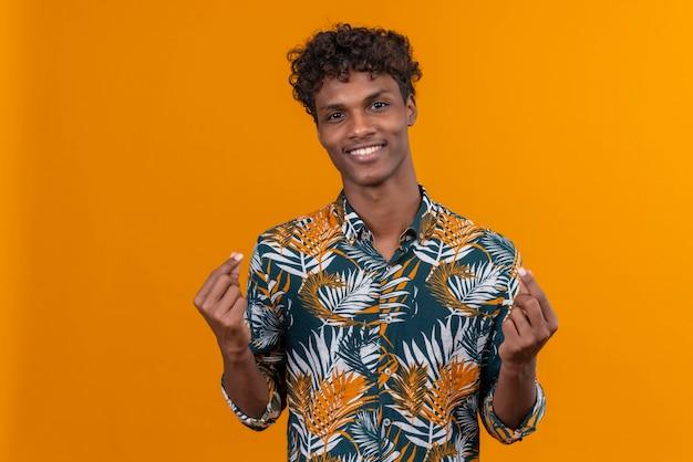 Een jonge, knappe, donkere man met krullend haar in een met bladeren bedrukt hemd met een perfect gebaar