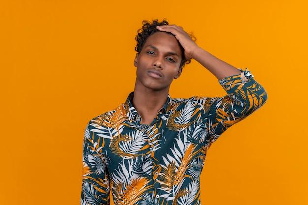 Een jonge, knappe, donkere man met krullend haar in een overhemd met bladerenprint en een gestreste en verwarde uitdrukking die de hand op het hoofd houdt