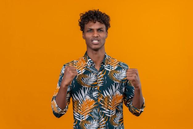 Een jonge knappe donkere man met krullend haar in een shirt met bladerenprint en een boos gezicht, hand in hand met gebalde vuisten