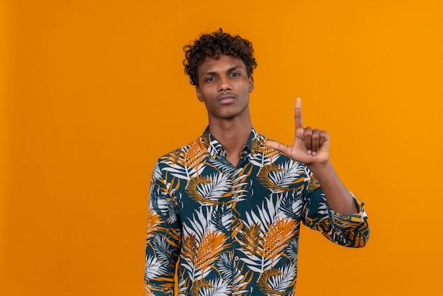 Een jonge, knappe, donkere man met krullend haar in een shirt met bladerenprint en een ernstig gezicht dat zijn hand opstak