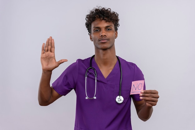 Een jonge knappe donkere mannelijke arts met krullend haar draagt een violet uniform met een stethoscoop en toont een papieren kaart met het woord nee