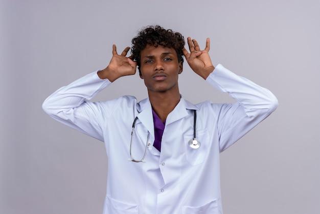 Een jonge knappe donkere mannelijke arts met krullend haar, gekleed in een witte jas met een stethoscoop hand in hand op het hoofd